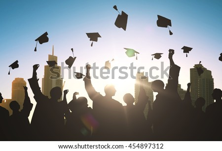 education, graduation and people concept - silhouettes of many happy students in gowns throwing mortarboards in air
