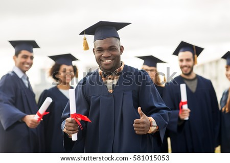 education, graduation, gesture and people concept - group of happy international students in mortar boards and bachelor gowns with diplomas showing thumbs up