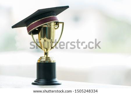 Education graduation in achievement success concept: Golden trophy cup winner and graduate hap on blur background. Achievement and success awards theme ideas. excellent challenge concepts