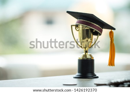 Education graduation in achievement success concept: golden trophy cup winner with graduate hap, rising money coins. Management study competition leadership have many moneys for learning