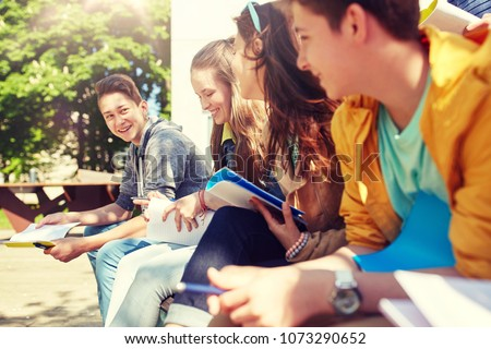 education, high school and people concept - group of happy teenage students with notebooks learning at campus yard #1073290652