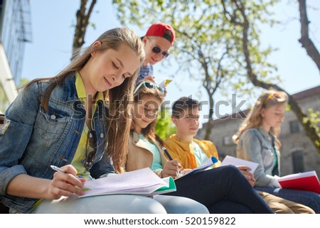 education, high school and people concept - group of teenage students with notebooks learning at campus yard