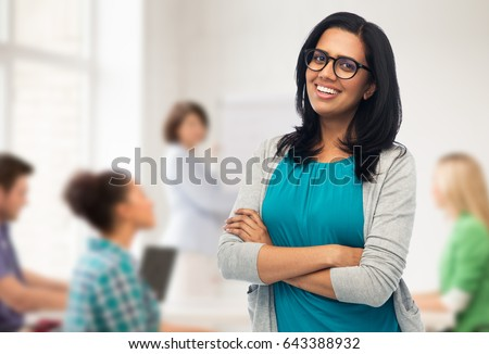 education, high school and people concept - happy smiling young indian woman or teacher in glasses over classroom background