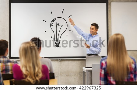 education, high school, teaching, idea and people concept - group of students and happy teacher with notepad showing light bulb drawing on white board in classroom