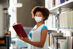 education, high school, university, learning and people concept - african american student girl wearing face protective medical mask for protection from virus disease reading book at library