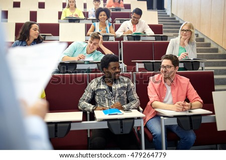 education, high school, university, learning and people concept - group of international students with notebooks talking at lecture hall #479264779