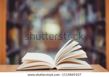 Education learning concept with opening book in old library, isle of bookshelves in school study class room background #1114869107