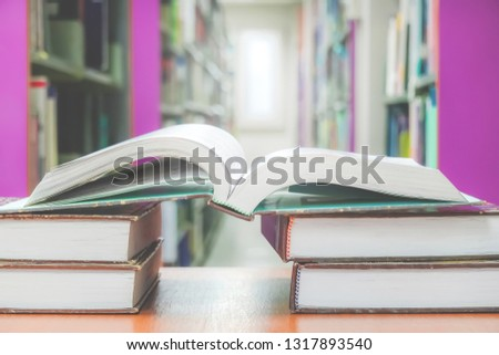 Education learning concept with opening book or textbook in old library and background bookshelf for education. #1317893540
