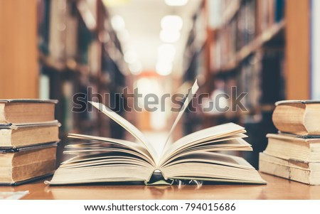 Photo of  Education learning concept with opening book or textbook in old library, stack piles of literature text academic archive on reading desk and aisle of bookshelves in school study class room background