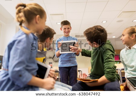 education, learning, technology, children and people concept - happy student boy showing tablet pc computer to group of kids at school #638047492