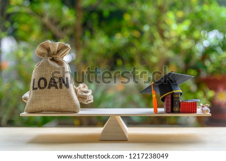 Education loan for study overseas / student loan concept : Mortarboard, loan bag on balance scale, depicts loans issued for the purpose of attending an academic university and pursuing academic degree