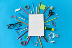 education, office and object concept - notebook and stationery or school supplies on blue background