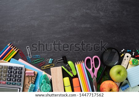 Education or back to school Concept. Top view of Colorful school supplies with books, color pencils, calculator, pen cutter clips and green apple on chalkboard background. Flat lay.