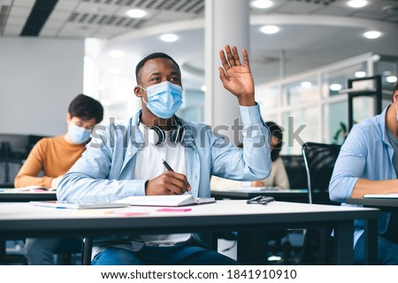 Education, Pandemic And Health Concept. African american male student raising hand for answer, wearing protective medical mask for protection from virus disease at high school lesson. New Normal
