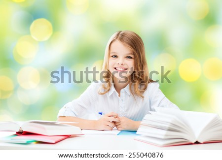 education, people, children and school concept - happy student girl sitting at table with books and writing in notebook over green lights background