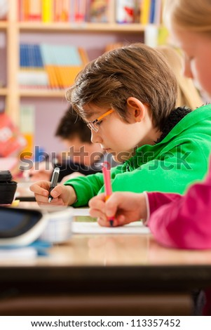 Education - Pupils at primary or elementary school doing their homework or having a school test
