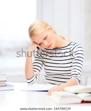 education, school and business concept - concentrated woman with books and notebook studying in college