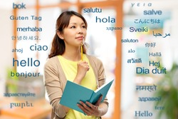 education, school and translation concept - asian student or creative woman with diary and pencil thinking over greeting words in different foreign languages