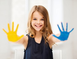 education, school, art and happiness concept - little student girl showing hands in yellow and blue color at school