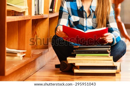 Education school concept. Clever female student girl sitting on floor in college library with stack books reading. Indoor