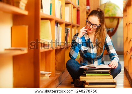 Education school concept. Clever female student long hair girl blue glasses sitting on floor in college library with stack books. Indoor