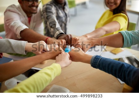 education, school, teamwork and people concept - close up of international students hands making fist bump gesture #499898233