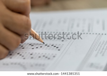 Education school test concept : Hands student holding pencil for testing exams writing answer sheet or exercise for taking fill in admission exam multiple carbon paper computer at university classroom #1441385351