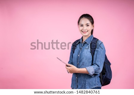Education study abroad, Asian Chinese student girl holding tablets looking to camera, happy mood smiling broadly,Young female student who studies in the school library on isolated pink background