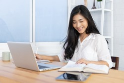 Education study abroad,Asian student girl sitting at table looking book while do homework with laptop making video call abroad using internet friend connection, happy mood smiling broadly in library