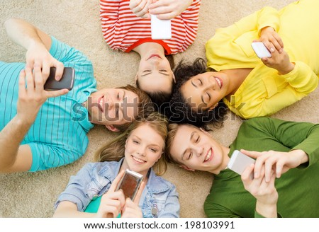 education, technology and happiness concept - group of young smiling people lying down on floor in circle with smartphones #198103991