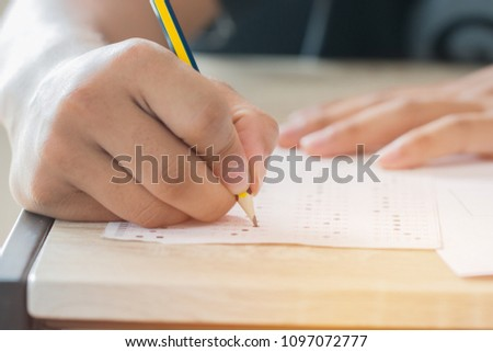 Education test concept : Man Hands high school, university student holding pencil for testing exams writing answer sheet and exercise for taking in exam paper on wood table at classroom with uniform #1097072777