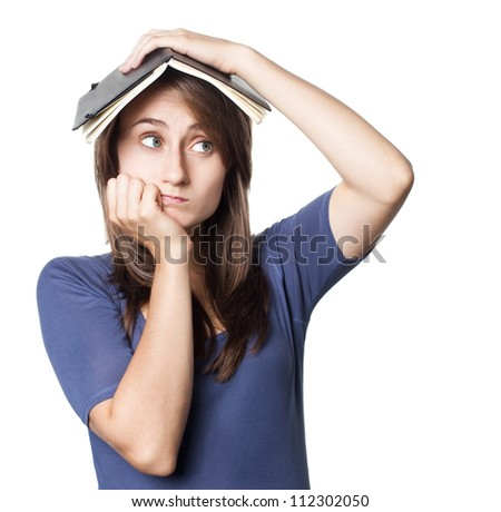 Education. Tired girl holds a notebook on her head on a white background with copyspace