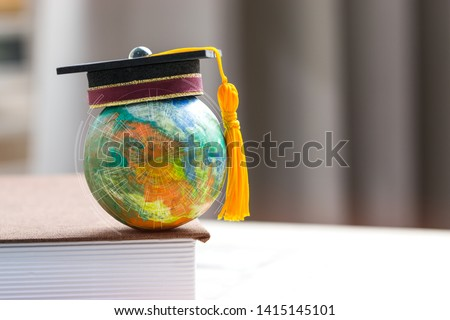 Education to learn study in world. Graduated student studying abroad international idea. Master degree hat on top globe book. Concept of graduate educational for long distane learning anywhere anytime