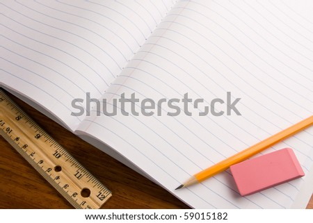 Education topic. Close up of notebook with pencil and eraser on top and a ruler on the side.