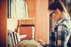 Education travel and geography concept. Hipster lovely woman female student in blue glasses in library with globe. Instagram filter
