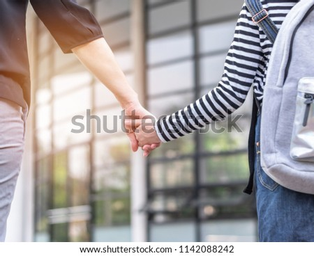Educational back to school, parent's day, bring kid to work concept with elementary student girl carrying backpack holding woman or mother's hand walking up admission office building going to class