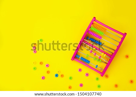 Educational colorful abacus beads for kids isolated on yellow background.Broken, learning equipment. Calculating thinking concept, with space for text