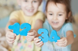 Educational colorful numeral figures in a child hands. Teaching children numbers. Happy children show numbers.