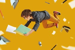 Educational concept. Smart boy teenager student preparing for lessons flies through the air surrounded by books and educational supplies. Yellow background with lights.