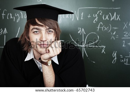 Educational theme: graduating student in academic gown in a classroom.
