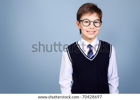 Educational theme: portrait of a schoolboy. Studio shot over grey background. - stock photo