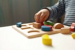 Educational toys, Cognitive skills, Montessori activity. Closeup: Hands of a little Montessori kid learning about color, shape, sorting, arranging by engaged colorful wooden sensorial blocks.