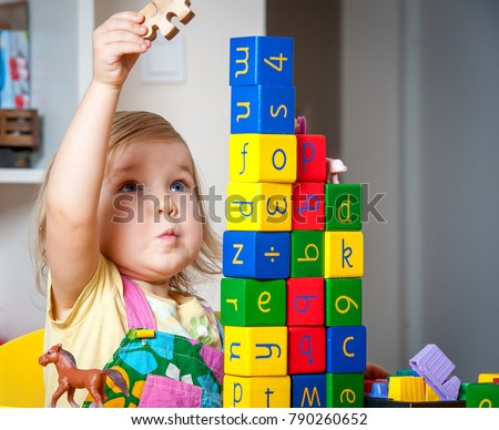Educational toys for preschool and kindergarten child. Cute little girl playing with blocks at home or daycare.