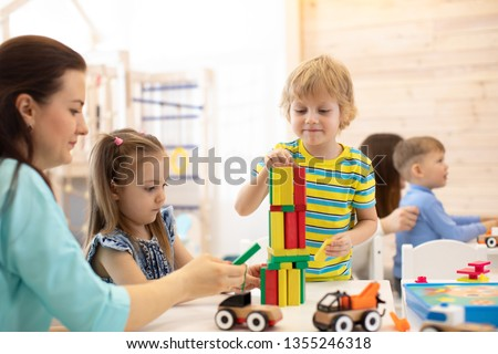 Educational toys for preschool and kindergarten children. Cute little kids playing with blocks in daycare center.