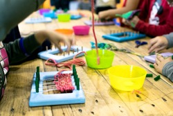 Educational weaving and knitting activity. Knitting wool for kids.