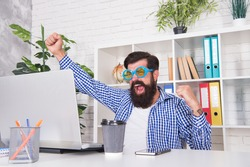 Eee. Happy hipster celebrate victory in Internet. Bearded man give winner gesture. Playing online video game. Winning real prize. Victory and success. Modern technology. Play and win.