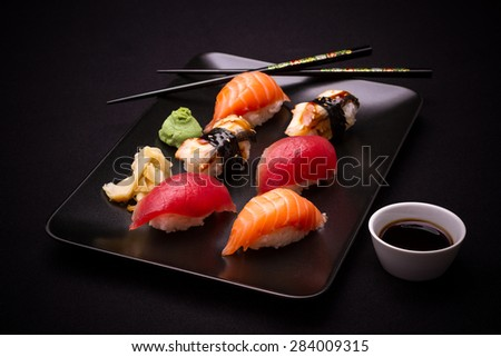 Eel, salmon and tuna sushi with chopsticks, dark background