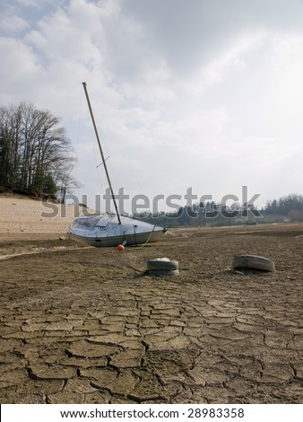 Effect of global warming: a boat on the bottom of a dry lakebed. Dried, cracked earth is the consequence of the climate change and global warming.