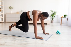 Effective bodyweight exercises. Curvy black woman making strength workout, running with her hands on floor at home. Plus size young lady training her body, leading active lifestyle