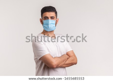 Effective protection against coronavirus. Man holding hands crossed and wearing hygienic mask to prevent infection, respiratory illness such as flu, 2019-nCoV, Covid-19. indoor studio shot, white back